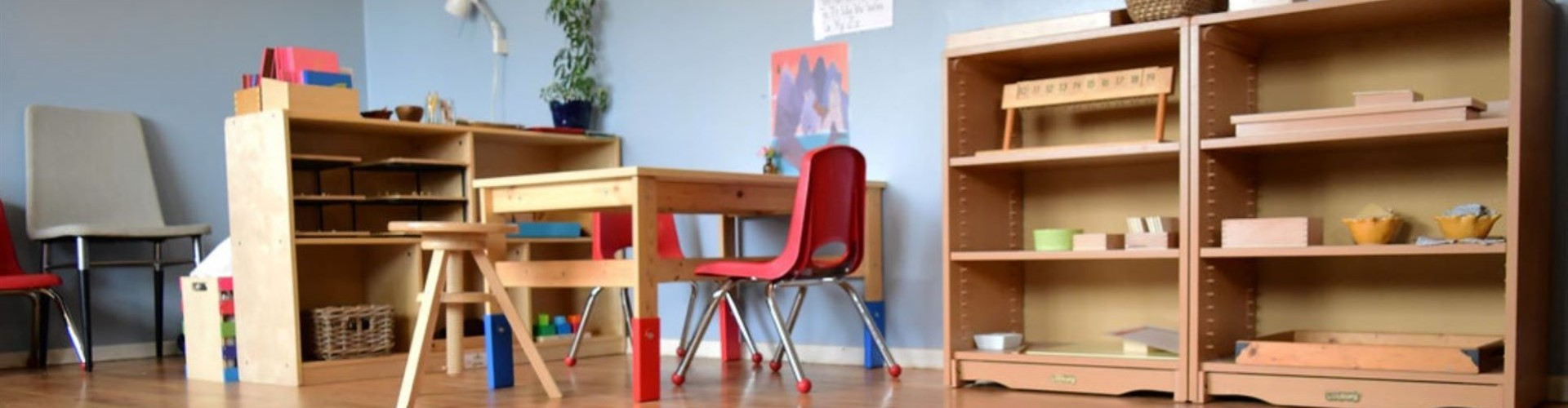 Montessori Classroom with shelves of materials and a table with a red chair and a stool.